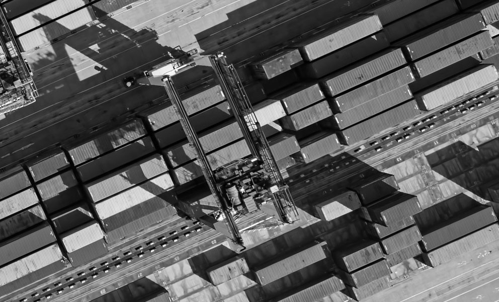 An aerial view of several cargo containers and cranes in a port.